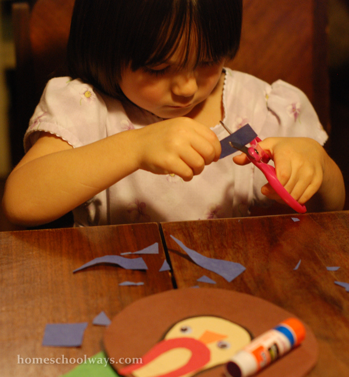 Small girl cutting paper with pink scissors