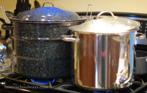 Water bath canner next to pot cooking applesauce