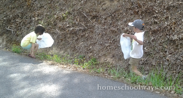 Boy and girl pick up trash in a ditch