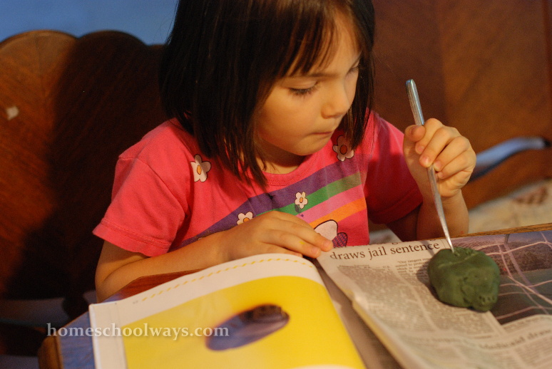 Little girl carving a scarab amulet