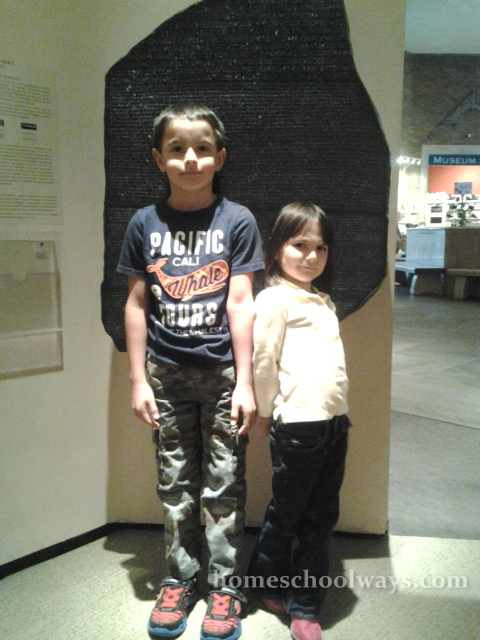 Boy and girl in front of a Rosetta Stone replica