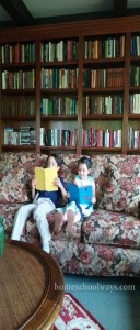 Boy and girl reading on a couch in a private library