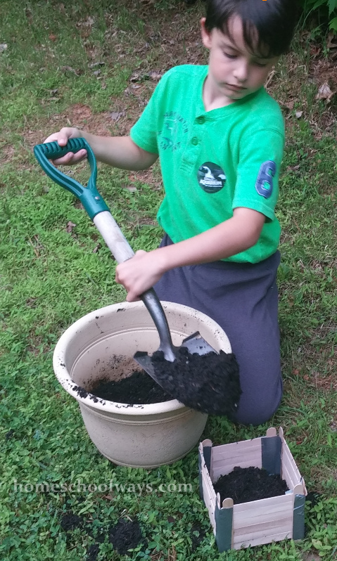 Boy building a dirt mold for a backyard Great Wall of China