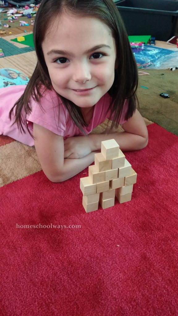Girl stacks a wooden block tower