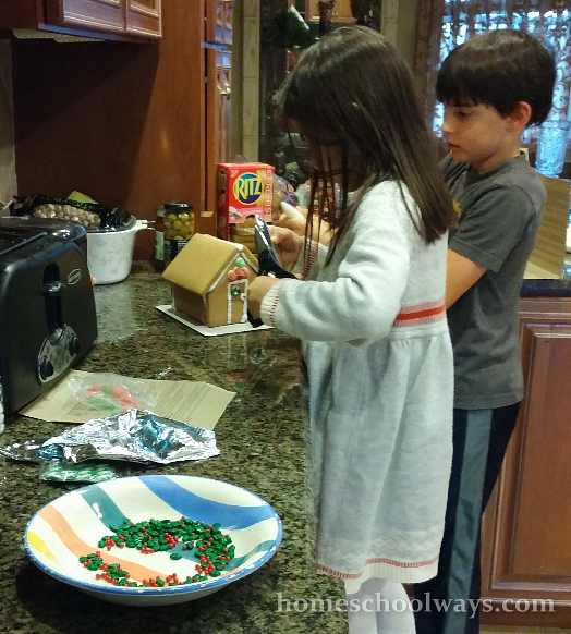Boy and girl decorating a gingerbread house