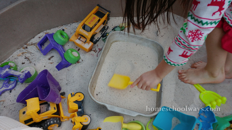 Girl gets sand from a sandbox