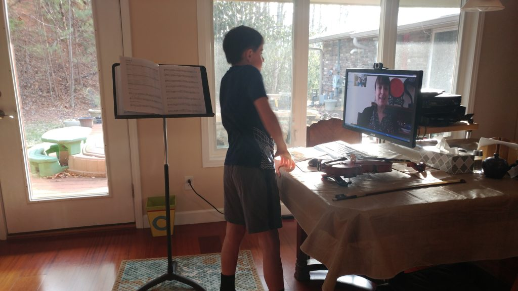 Boy talking to violin teacher via Skype